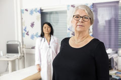 Confident Senior Patient Standing With Doctor In Background. Portrait of confident senior patient standing with doctor in background at clinic stock photos