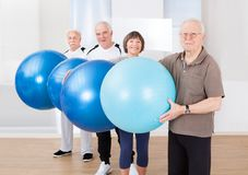Confident senior people carrying fitness balls Royalty Free Stock Photo