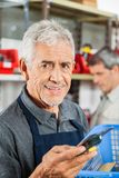 Confident Senior Salesman Holding Tool In Store Royalty Free Stock Photography