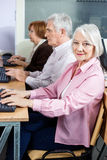 Confident Senior Woman In Computer Class. Portrait of confident senior women sitting in computer class with classmates at desk Royalty Free Stock Photos
