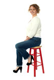Confident senior woman resting on stool Royalty Free Stock Photography