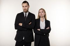 Confident serious businesspeople posing in black suits, standing with crosed hands, looking at camera stock images