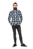 Confident serious hipster in plaid tartan blue shirt with hands in pockets. Full body length portrait isolated over white studio background Stock Image