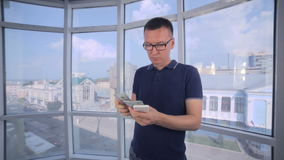 Confident, serious man counting money, US dollars using smartphone. HD stock footage