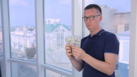 Confident, serious man counting and showing money, US dollars into camera. HD stock footage