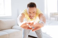 Confident serious man incorporating stretching in training royalty free stock image