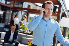 Confident serious man listening to his interlocutor. Phone call. Confident nice handsome men putting a phone to his ear and listening to his interlocutor while Royalty Free Stock Images