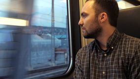 Confident serious man looks out the window of a train. stock footage