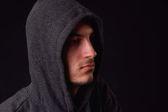 Confident and serious young man wearing black hoodie on a black. Background. Studio shot Stock Photography