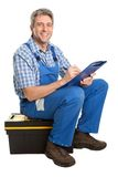 Confident service man taking notes. Confident service man sitting on toolbox and taking notes. Isolated on white Stock Photos