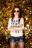 Confident sexy woman in sunglasses posing on golden background Royalty Free Stock Image