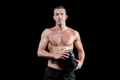 Confident shirtless man holding nutritional supplement. Portrait of confident shirtless man holding nutritional supplement against black background Stock Image