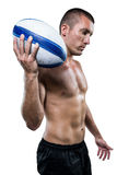 Confident shirtless rugby player holding ball Royalty Free Stock Photography