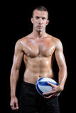 Confident shirtless sports player holding ball Royalty Free Stock Photos