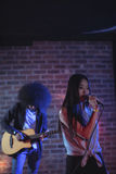 Confident singer with guitarist performing in nightclub. Confident female singer with male guitarist performing in nightclub Royalty Free Stock Images