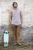 Confident Skateboarder Leaning On Wall Stock Image