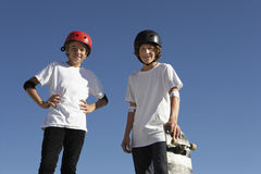 Confident Skateboarders Standing Against Blue Sky Stock Photography
