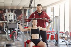 Confident slim beautiful young lady sits on fitness station, does physical exercises, looking directly at camera. Athletic tall royalty free stock photo