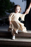 Confident small girl. Small girl in dress descending stairs and holding mom's hand Royalty Free Stock Photos