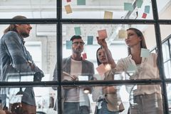 Confident and smart. Group of young modern people in smart casual wear using adhesive notes while standing behind the glass wall stock photo