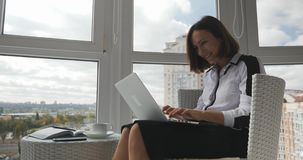 Confident smart young business woman looking at monitor on laptop, waiting for solution and happy about deal with business partner. S that was successfully stock footage