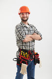 Confident smiley workman. With tools in orange helmet standing over light background Royalty Free Stock Photo