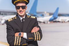 Confident smiling aviator outside of airport. Assured pilot wearing uniform is standing afore planes. He crossing hands and looking at camera with bright smile Stock Photography