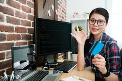 Business woman designing online safety system. Confident smiling business woman designing online safety system and showing credit card with ok gesture looking at Royalty Free Stock Photos