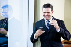 Confident smiling businessman holding mobile phone Royalty Free Stock Photos
