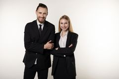 Confident smiling businesspeople posing in black suits, standing with crosed hands, looking at camera stock photo