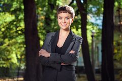 Confident smiling businesswoman keeping arms crossed outdoors Royalty Free Stock Photography