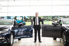 Confident smiling car salesman at the showroom near two cars, he is standing near open cars doors of luxury cars royalty free stock image