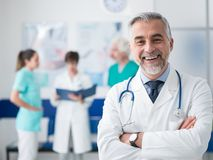 Confident doctor posing at the hospital. Confident smiling doctor posing and the hospital with arms crossed and medical team working on the background royalty free stock images