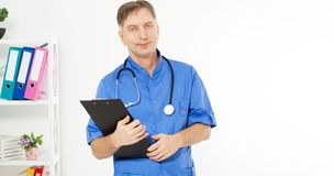 Confident smiling doctor posing and looking at camera with black folder, medical office clinic on the background, copy space stock photography