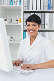Confident smiling female doctor using computer Royalty Free Stock Images