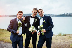Confident smiling handsome groom in black suit with two groomsma. N Stock Photo
