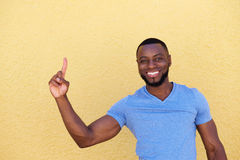 Confident smiling man pointing finger up Stock Images
