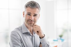 Confident smiling man posing in the office and smiling at camera stock photography