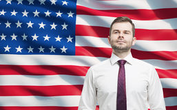 Confident smiling man. United States flag as a background. Royalty Free Stock Image