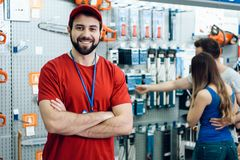 Confident smiling salesman in power tools store. Guy is ready to help clients. Confident smiling salesman on foreground in power tools store. Guy is ready to stock photo