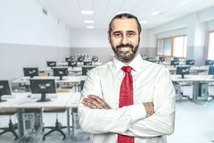 Confident smiling teacher. Confident teacher and classroom background stock image
