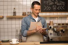 Waiter taking notes. Confident smiling waiter taking notes while working in cafe Stock Image