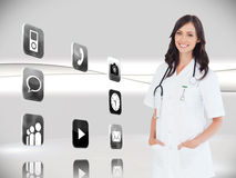 Confident and smiling woman doctor standing in front of the window Stock Photos