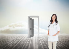 Confident and smiling woman doctor standing in front of the window Royalty Free Stock Photo