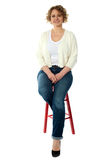 Confident smiling woman sitting on stool Stock Photo