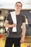 Confident and smiling young man exercising at fitness gym Stock Photo