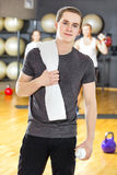 Confident and smiling young man exercising at fitness gym Stock Photography