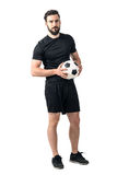 Confident soccer of futsal player holding ball with daring look at the camera Royalty Free Stock Photo