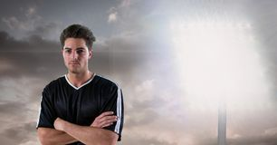 Confident soccer player with arms crossed against floodlight Stock Photos
