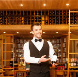 Confident sommelier. Cheerful young sommelier holding a wine bottle and pointing it Royalty Free Stock Image